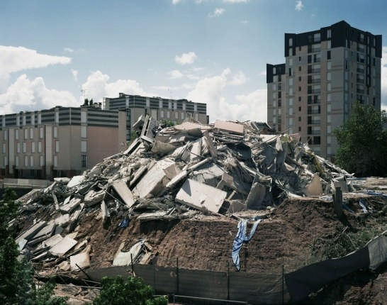"<i>Cairns</i> (251/261 Résidence Provence, Dammarie-lès-Lys, 1973–2008) 2008. <br /><i>Cairns</i> is the title of a series of photographs depicting the aftermath of the demolition of high-rise public housing in Glasgow and the Parisian suburbs. The visual language connects to that used by photographers of the Düsseldorf school, from Bernd and Hiller Becher to Andreas Gursky and Thomas Struth. The word ""cairn"" indicates ""a pyramid of rough stones raised as a memorial"". Courtesy Cosmic Galerie (Bugada & Cargnel), Paris"