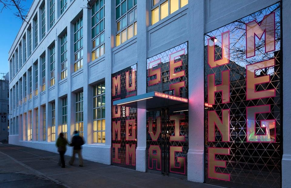 The semi-transparent storefront entrance, with its triangular motif and oversize pink-edged lettering, is the first screen that visitors encounter. ©Peter Aaron. Courtesy of Museum of the Moving Image