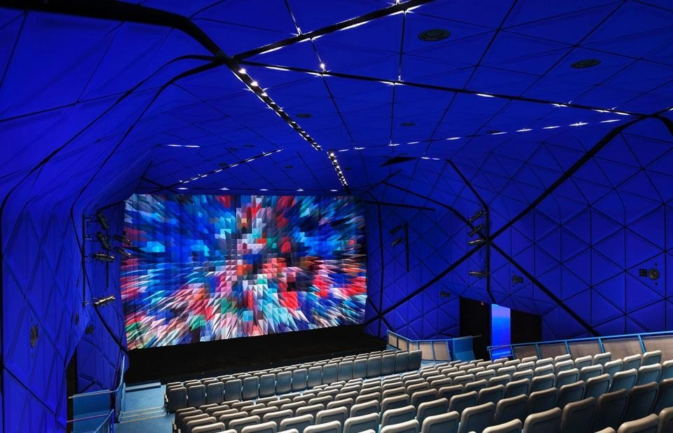 The 264-seat theater is a luminous cocoon whose walls and ceiling are wrapped in blue felt. ©Peter Aaron. Courtesy of Museum of the Moving Image
