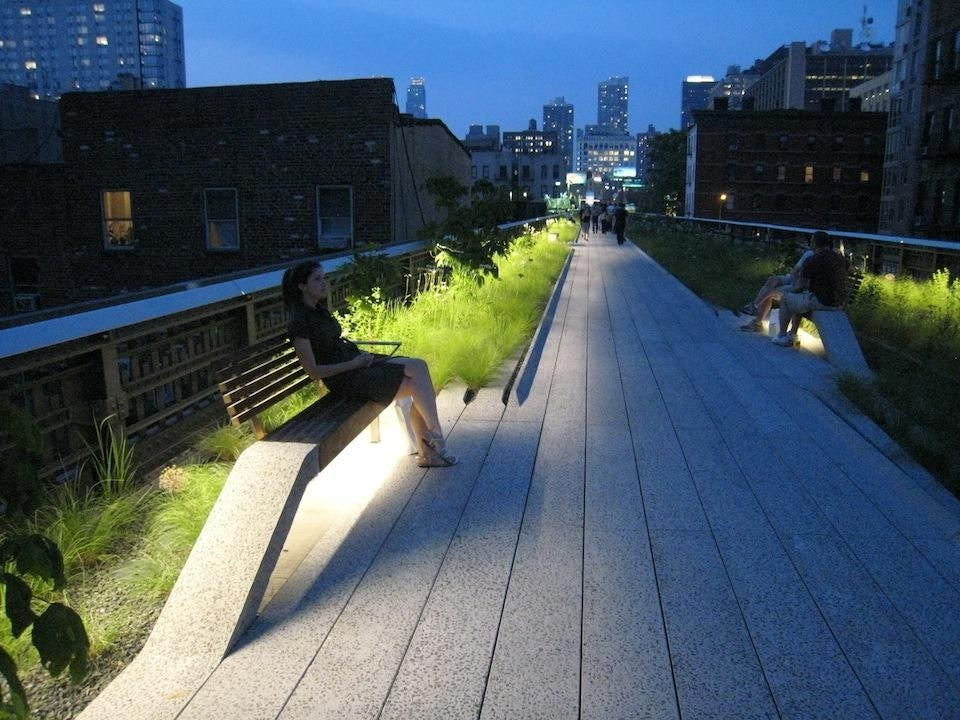 The linear wildflower garden at dusk, with plantings illuminated and benches peeling up from the 12-in. (30.5cm)-wide concrete planks. © Gideon Fink Shapiro.