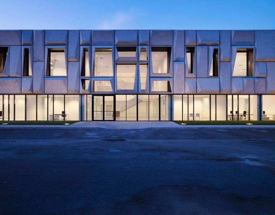 A three-dimensional tectonic façade rests on a transparent and light base letting the new headquarters for a clothing company in Nola's industrial suburbs.