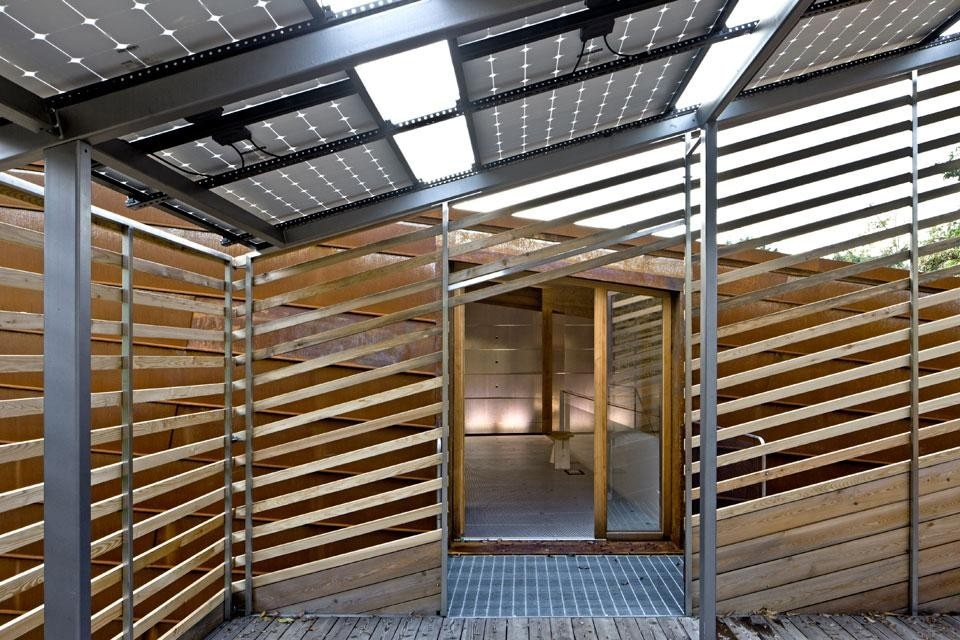 The wood structure supports a sequence of photovoltaic panels