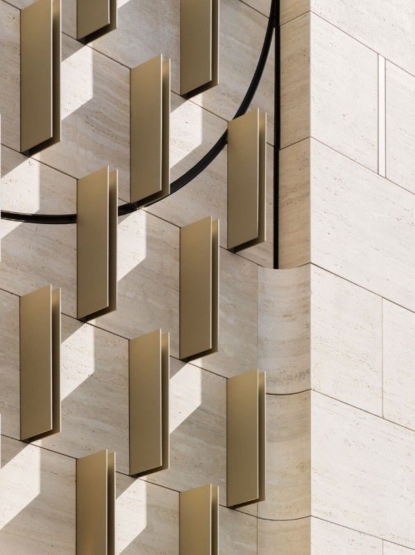Detail of the facade in travertine marble and brass details