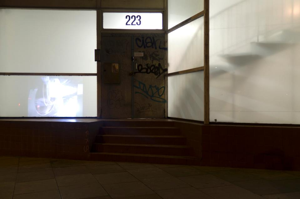 Top image: The entrance to <i>Between Bridges</i>  (former studio of Wolfgang Tillmans in London). <br />Above: The video <i>Visions (Bollard)</i> projected on the opaque glass of the gallery, visible from the street and from within.