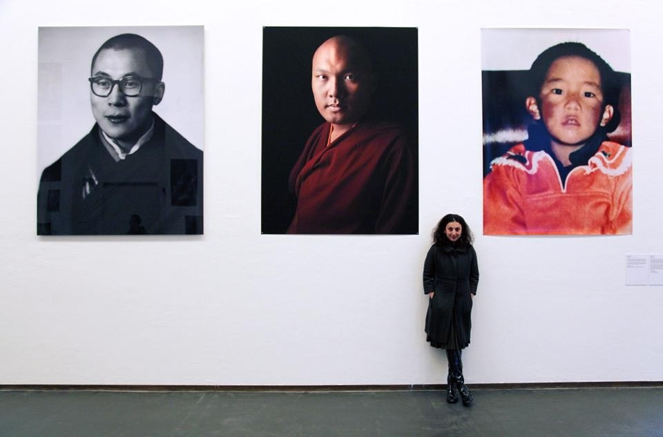 Paola Pivi, <em>Tulkus 1880 to 2018</em>, 2012. Portrait of the artist. In the background, left, the 14th Dalai Lama at the age of 22, in a 1957 portrait by Kinsey Brothers, Delhi. Courtesy of the Newark Museum. Centre, the 17th Karmapa in a 2012 photo by David Zimmerman. Right, the eleventh Panchen Lama, who was made to disappear by the Chinese government only three days after he was recognized by His Holiness the Dalai Lama in 1995
