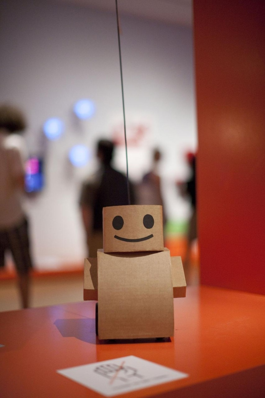 Kacie Kinzer. Interactive Telecommunications Program, Tisch School of the Arts, New York University. <i>Tweenbot,</i> 2009. Cardboard, paper, ink, batteries, motor, and wheels.  Installation view at The Museum of Modern Art, 2011. Photo © Scott Rudd.