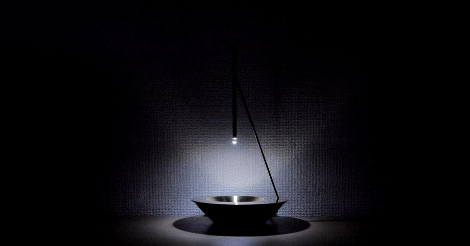 Top: One For All by Yuri Naruse and Jun Inokuma. Above: Dew is an elegant lamp by Vitro driven by a few ounces of water in a small brass bowl. Falling slowly through a pipe with an LED inside, the drops act as a lens and turn the light projected by the LED into a circle of moving light.