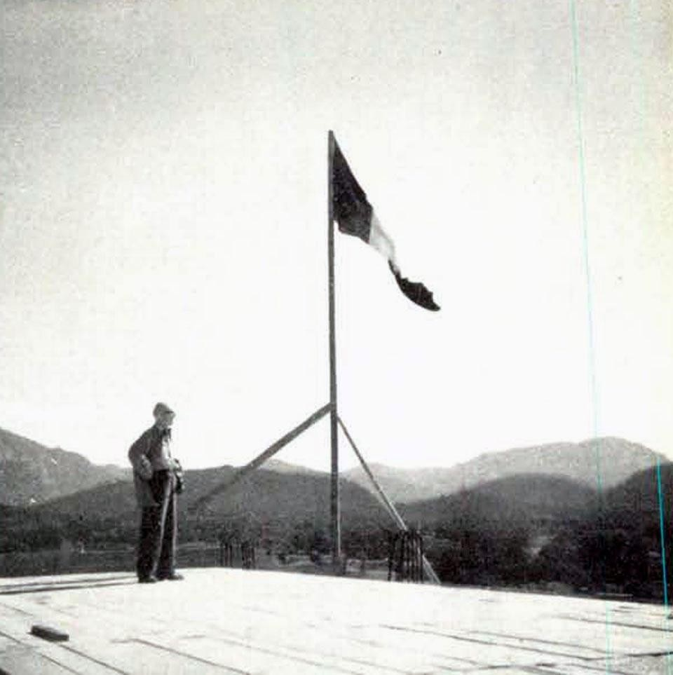 "Le Corbusier and the flag raised above the ""Unité d'habitation,"" October 6, 1949."