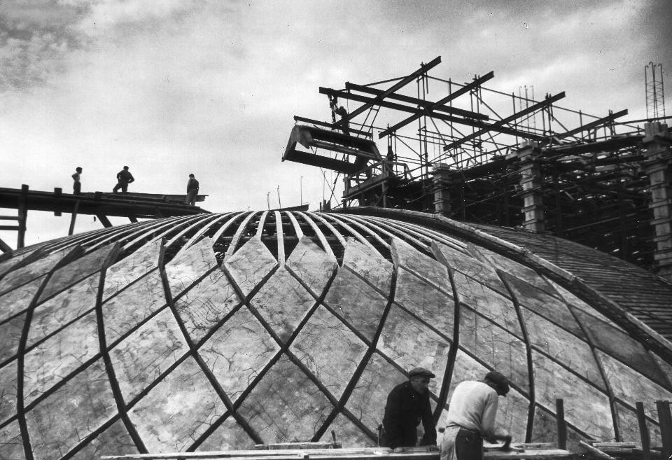 The roof of the hall during construction. Note the scale of human figures in the vast frame of the structure