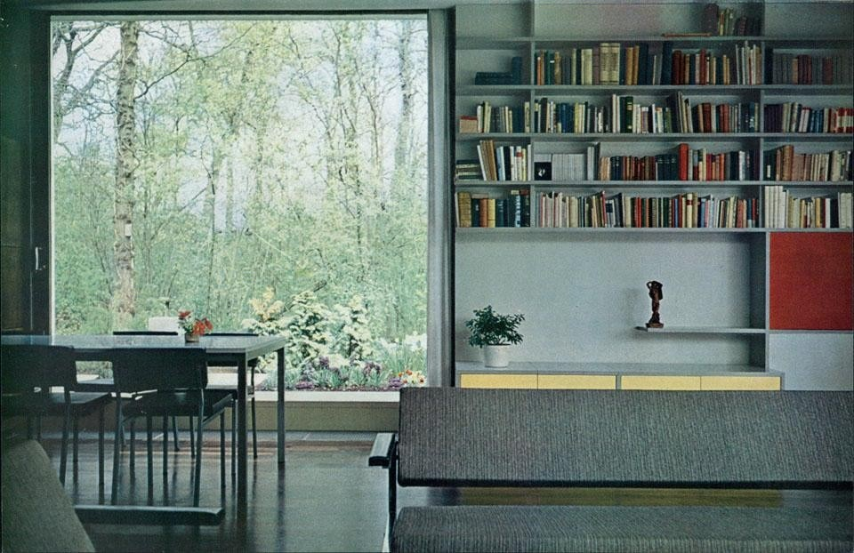 The large living room includes the kitchen within its volume; the only diaphragm is the wall/cabinet composed of a series of square shelves that open on both sides.