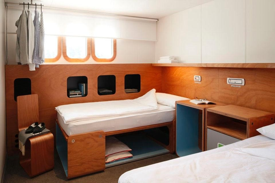 Cabin interior with single bed configuration.