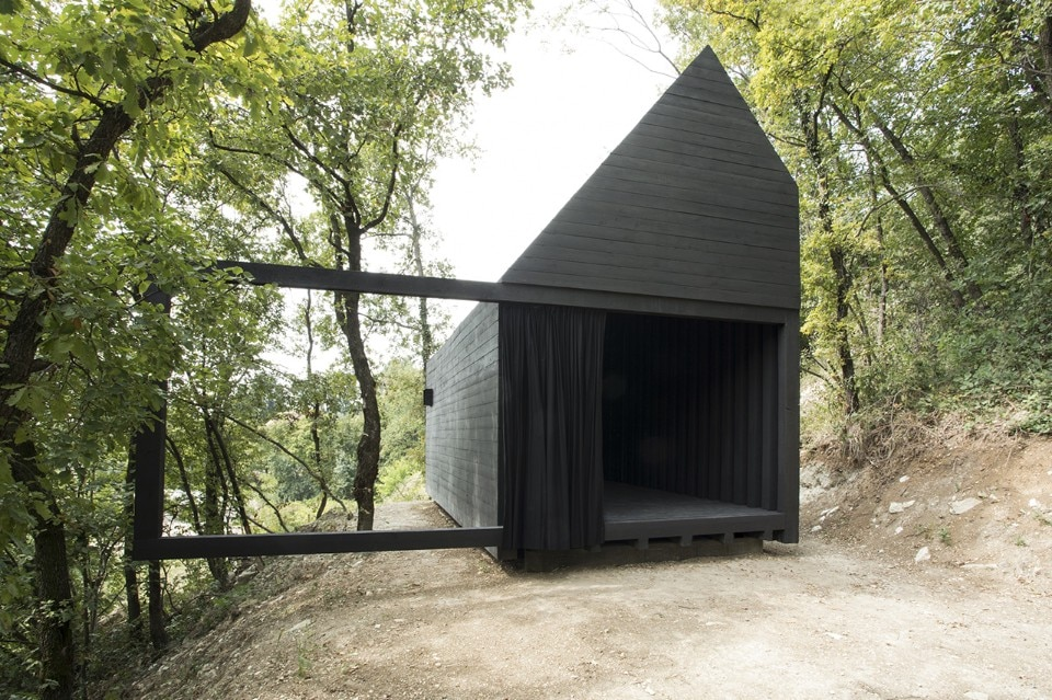 A black chapel between the forest and the vineyards